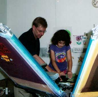 Brad Carlson teaching a young girlscout to screen print her own design.